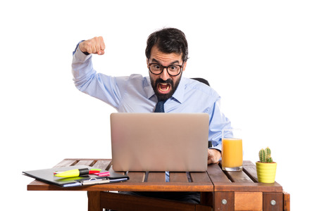 Businessman in his office giving punch over white background photo