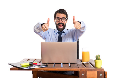 Businessman in his office with thumb up photo