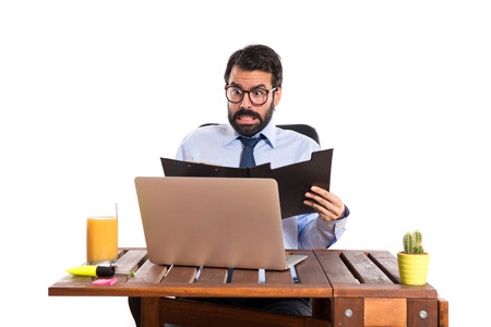 Surprised businessman in his office with his folder photo