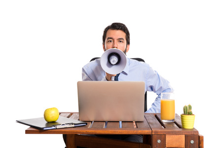 Businessman in his office shouting by megaphone photo