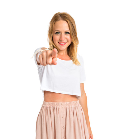 Blonde woman pointing to the front over white background photo