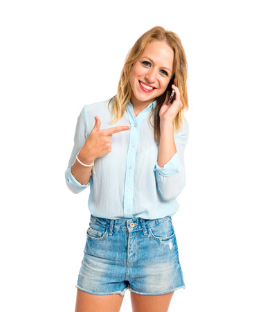 Blonde girl talking to mobile over white background photo