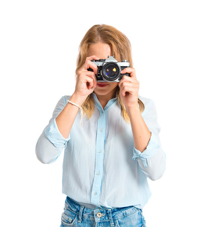 Blonde woman photographing over white background photo