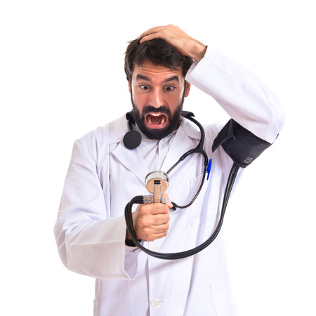 Frustrated doctor with blood pressure monitor over white background photo