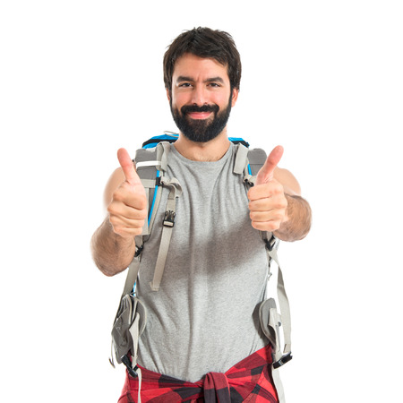 Backpacker with thumb up over white background photo