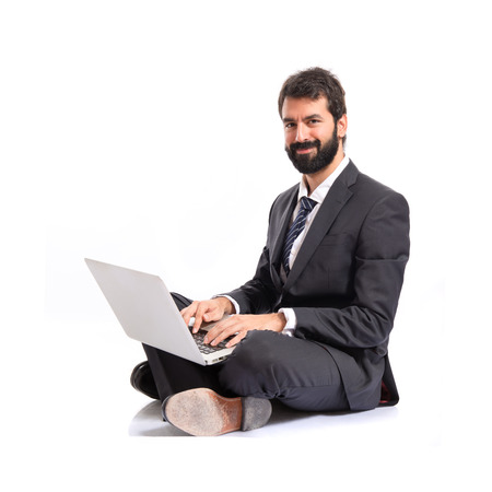 Happy businessman with laptop over isolated white background photo