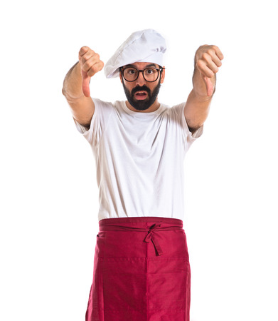 Chef doing a bad signal over white background photo