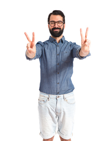 Young hipster man doing victory gesture photo