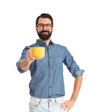 Young hipster man holding a cup of coffee photo