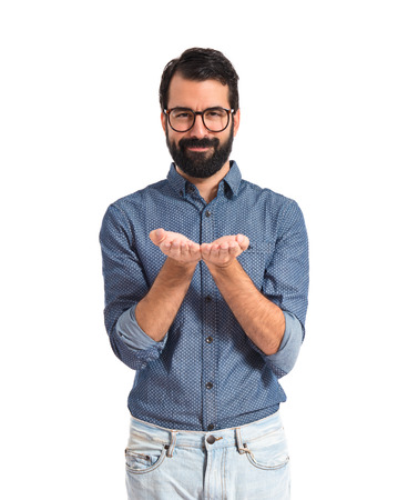 Young hipster man holding something over white  photo