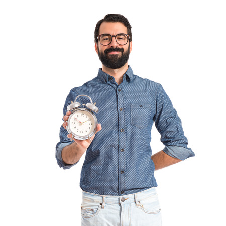 Young hipster man holding a clock photo