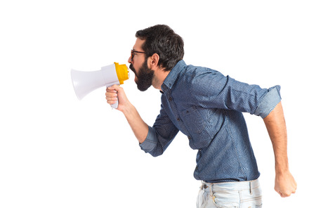 Young hipster man shouting by megaphone photo