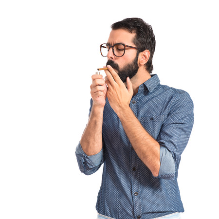 Young hipster man smoking over white  photo