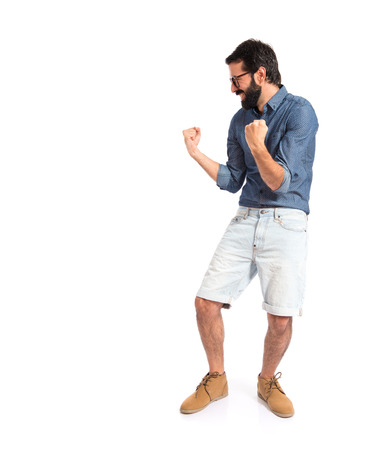 Lucky young hipster man over white  photo