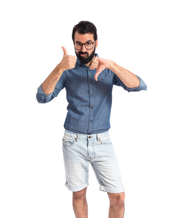 Young hipster man making a good-bad sign photo