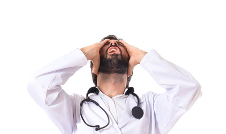 Frustrated doctor over isolated white background photo