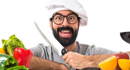 Crazy hipster chef with several vegetables and fruits photo