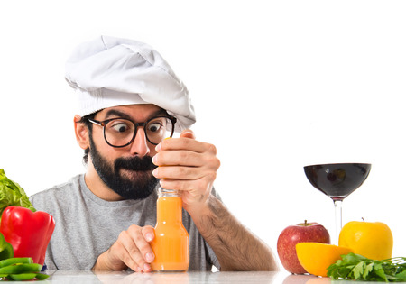 Crazy hipster chef making orange juice photo