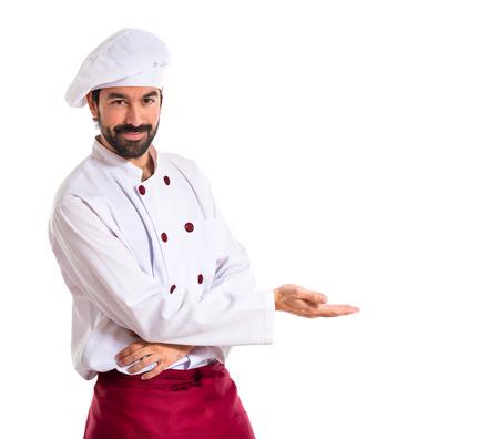 Cocinero que presenta algo más de fondo blanco Foto de archivo