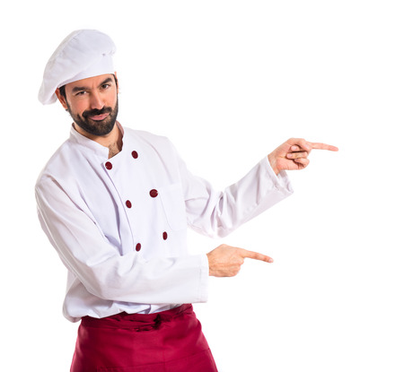 Chef pointing to the lateral over white background Standard-Bild