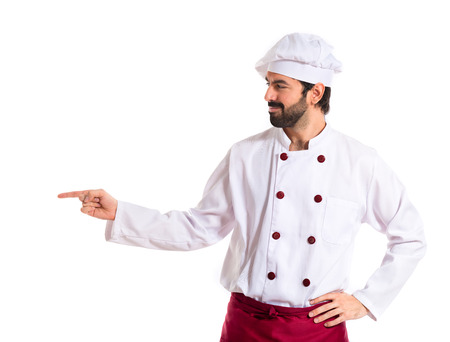 Chef pointing to the lateral over white background photo