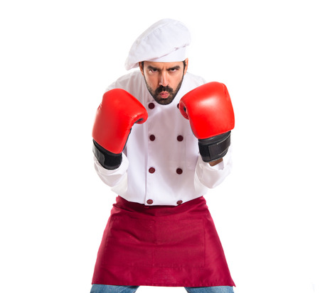Chef with boxing gloves over white background photo