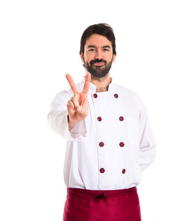 Chef doing victory gesture over white background photo