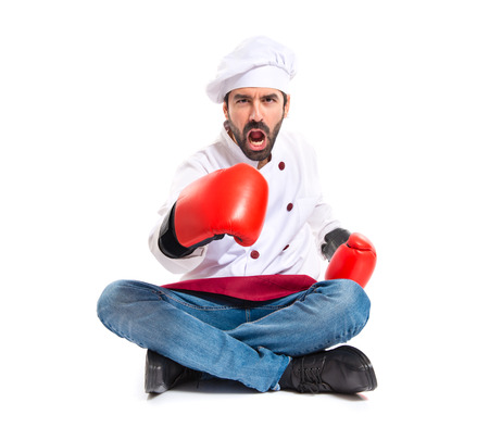 Chef with boxing gloves sitting on the floor photo