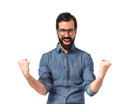 Lucky young hipster man over white background