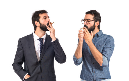 Man smoking with his brother over white background photo