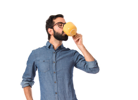 Young hipster man holding a cup of coffee