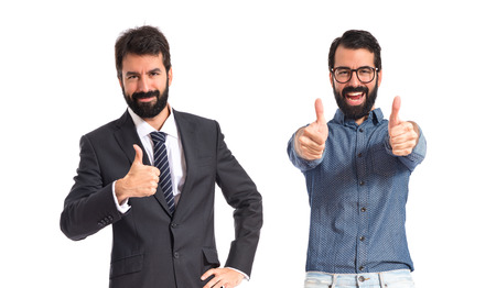 Twin brothers doing victory gesture over white background photo