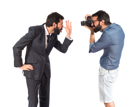 mockery: Man photographing his brother making a mockery