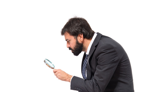 Businessman with magnifying glass over white background Stock Photo