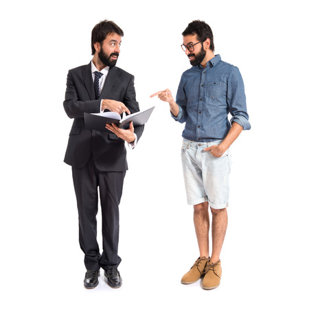 Twins with book over white background photo