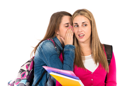 Student women whispering over white background photo