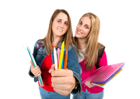 Students holding crayons over white background photo