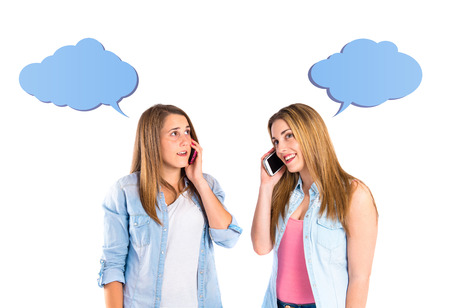 Young girls talking to mobile over white background photo