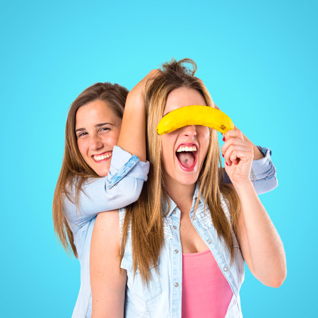 Friends playing with fruits over blue background photo