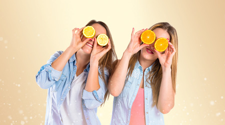 Friends playing with fruits over yellow background photo
