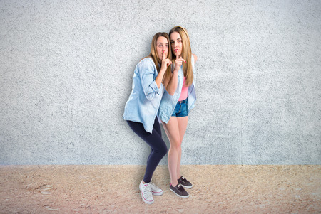 Friends making silence gesture over textured background photo