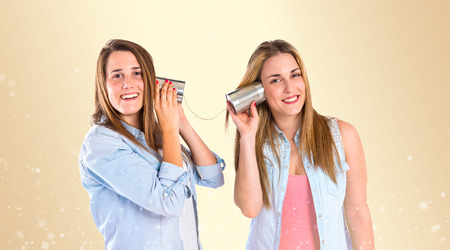 Friends talking through a tin phone over yellow background photo