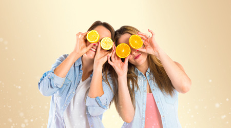 Girl playing with fruits over yellow background photo