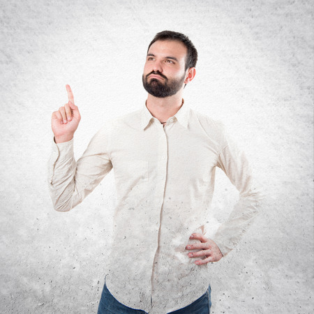 man pointing up: Young man pointing up over white background