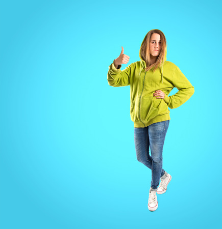 Girl with thumb up over blue background photo