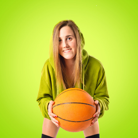 Blonde girl playing basketball over green background photo