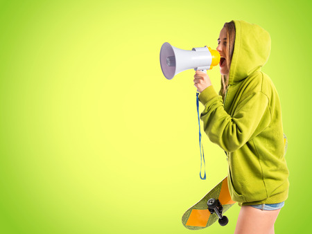 Young girl shouting over green background photo