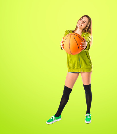 Pretty young girl wearing urban style with basketball photo
