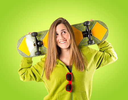 Skater with green sweatshirt over green background photo