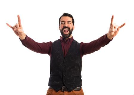 waistcoat: Man wearing waistcoat making horn gesture